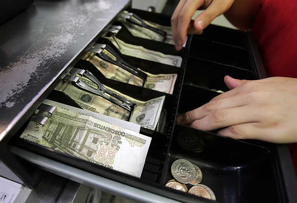Mexican currency is seen in the cash register drawer alongside US dollars as a cashier at Pizza Patron makes change for a customer in Dallas, Texas, United States.