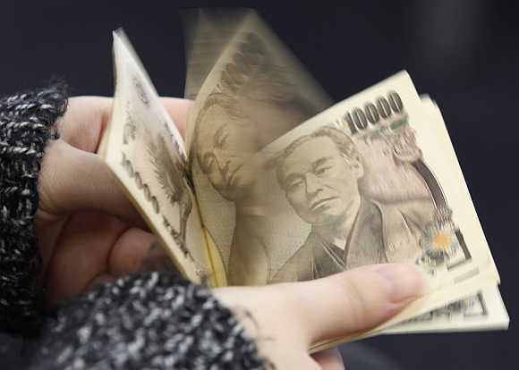 A woman counts Japanese 10,000 yen notes in Tokyo, Japan.