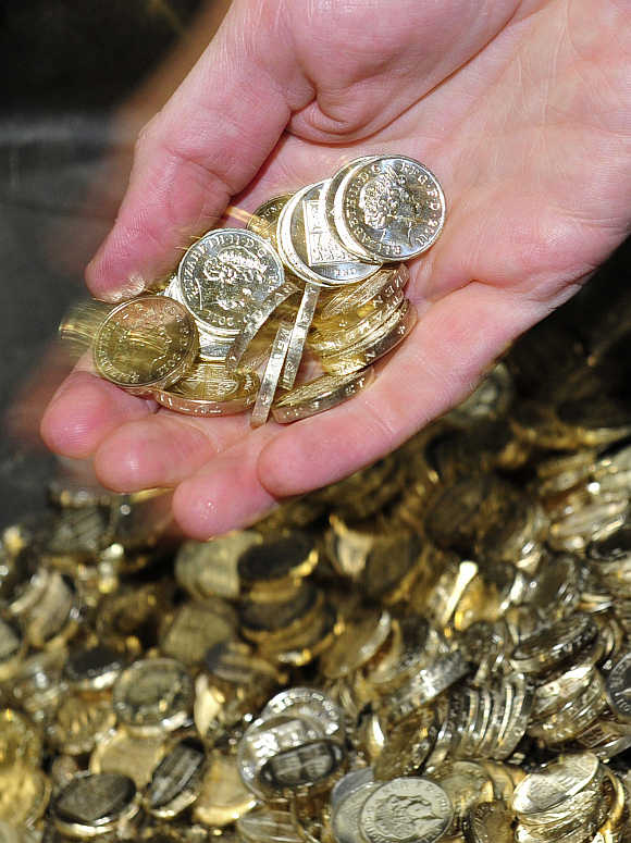 Britain's Chancellor of the Exchequer, George Osborne, handles newly minted one pound coins during a visit to the Royal Mint, in Cardiff.