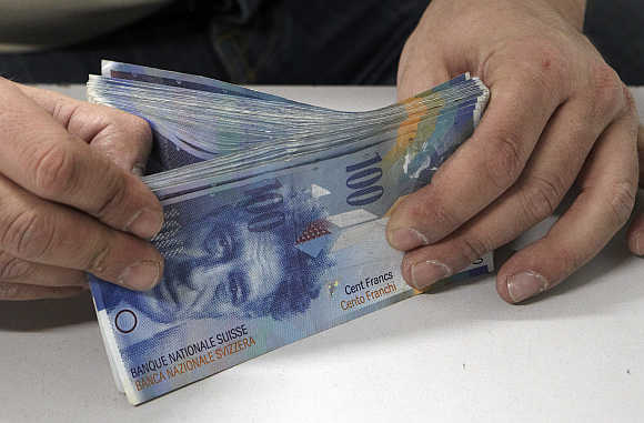 An employee handles 100 Swiss franc notes in the Canton of Vaud Bank near Lausanne, Switzerland.
