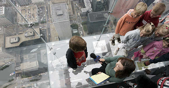 Ten-year-old Adam Kane, of Alton, Illinois, is interviewed by a television reporter as they stand on 'The Ledge', a five-sided glass box, 1,353ft  above the street in Chicago, United States.