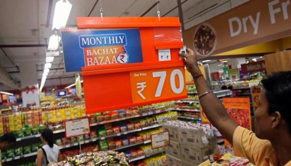 An employee changes the price tag of a product at the Big Bazaar retail store in Mumbai.