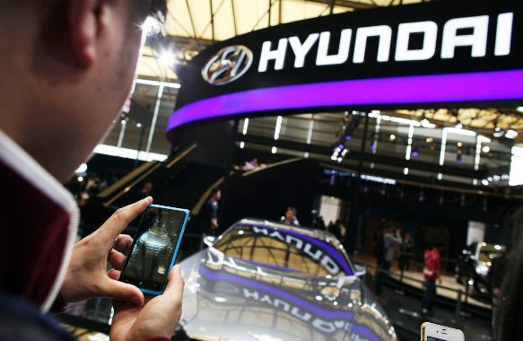 A man takes pictures of a Hyundai car during the 15th Shanghai International Automobile Industry Exhibition in Shanghai.