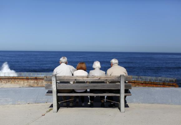 A pair of elderly couples view the ocean and waves along the beach in La Jolla, California.