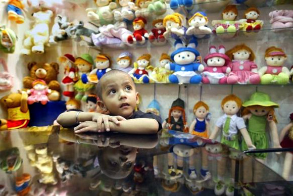 Kunal, a four-year-old Indian boy, looks at dolls at an exhibition in Kolkata.