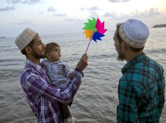 Mohammed (L), 25, holds a paper windmill aloft as he wades in the waters of the Arabian Sea with his son Mortaza and brother Taher in Mumbai.