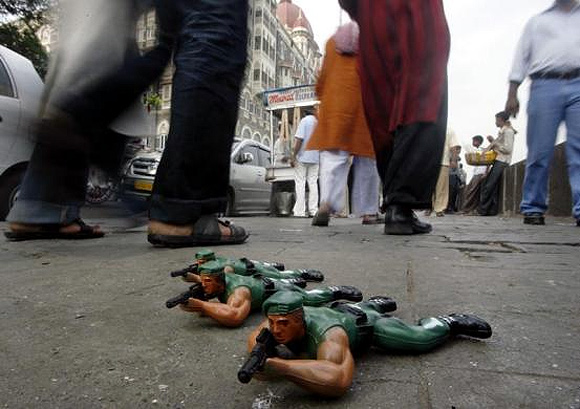 Toy soldiers are displayed for sale by a street hawker in front of the Taj Mahal Hotel.