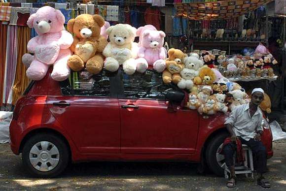 Stuffed toys are arranged on a parked car as a vendor waits for customers in Chennai.