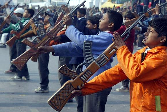 School children with toy guns perform during the full dress rehearsal for the Republic Day parade in Lucknow.