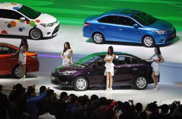 Models pose by Toyota cars during the 15th Shanghai International Automobile Industry Exhibition in Shanghai.