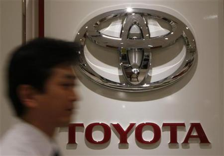 A man walks past a logo of Toyota Motor at its dealers shop.