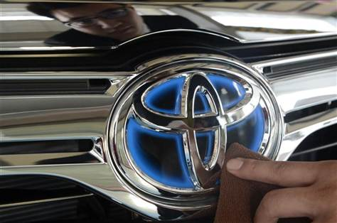 A worker cleans the logo of a Toyota car at dealership store in Taiyuan.