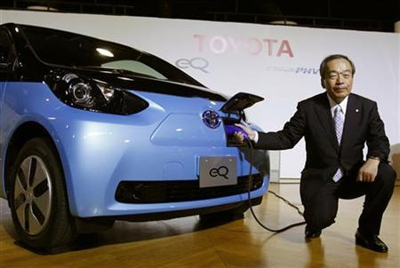 Toyota Motor Corp's Executive Vice President Takeshi Uchiyamada poses next to the company's newly developed compact electric vehicle eQ after a news conference in Tokyo.