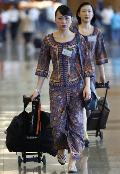 Singapore Airlines flight attendants walk through the terminal at an airport.