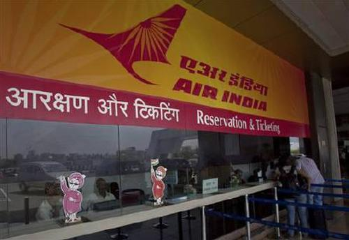 Passengers speak to ticketing staff through the only open counter at the Air India ticket office at the domestic airport in Mumbai.