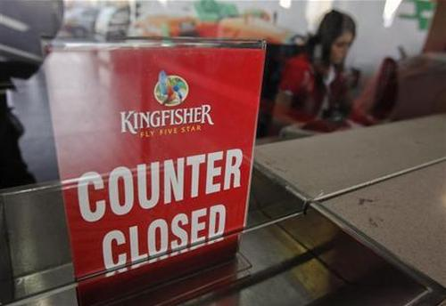 An employee of Kingfisher Airlines works next to a ''counter closed'' sign at their booking office at Mumbai's domestic airport.