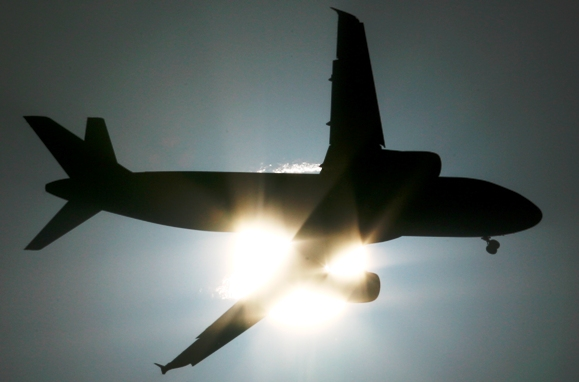 A passenger aircraft is silhouetted against the setting sun in New Delhi.