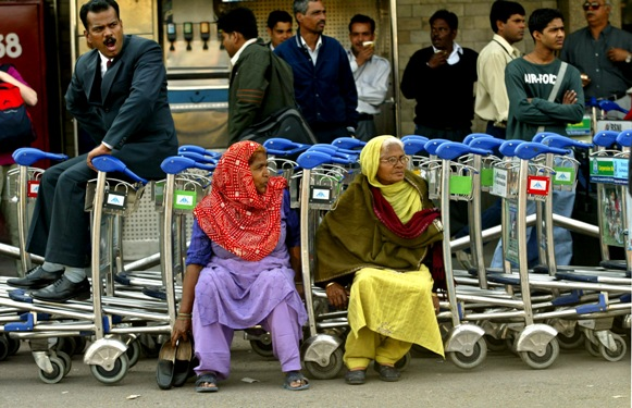 Employees of Airports Authority of India rest on trolleys during a protest in New Delhi.