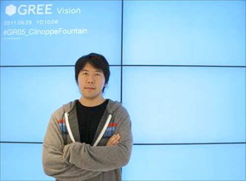 Gree Chief Executive Officer Yoshikazu Tanaka poses at his company's lobby.