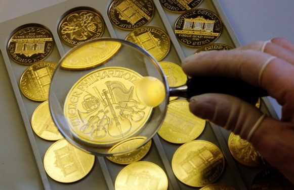 A worker at the Austrian Mint checks a gold Vienna Philharmonic bullion coin.