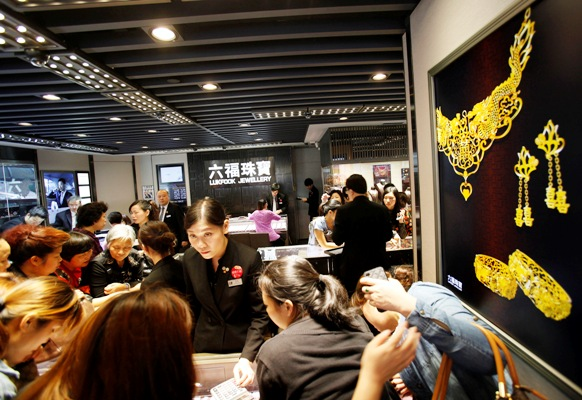 Attendants serve customers inside a jewellery store at Hong Kong's Mongkok district.