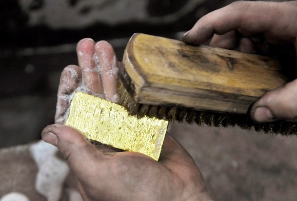 A worker brushes a gold bar.