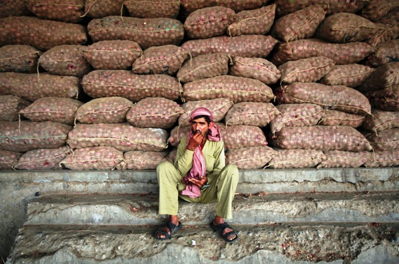 A labourer sits in front of stacked sacks of onions at a wholesale vegetable market.