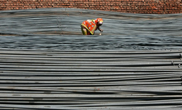 A labourer works inside an iron factory.