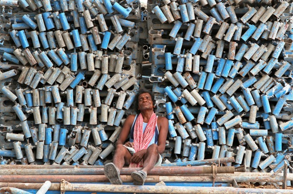 A worker takes a nap beside a stack of iron pipes at the construction site of a commercial complex in Chennai.
