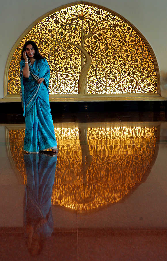 A woman talks on a mobile phone as she stands near a wood carving at a hotel lobby in New Delhi.