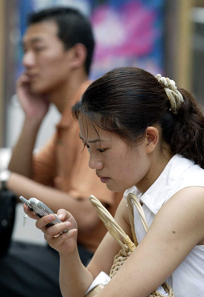 A woman sends text messages while a man chats on his mobile phone in Shanghai, China.