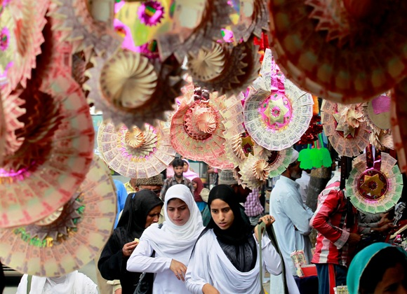 Kashmiri college girls walk under garlands made of Indian currency notes on display at a market in Srinagar.