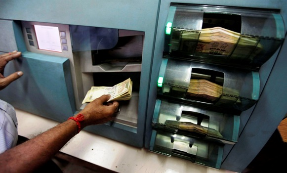 An employee checks Indian currency notes inside a bank in Kolkata.