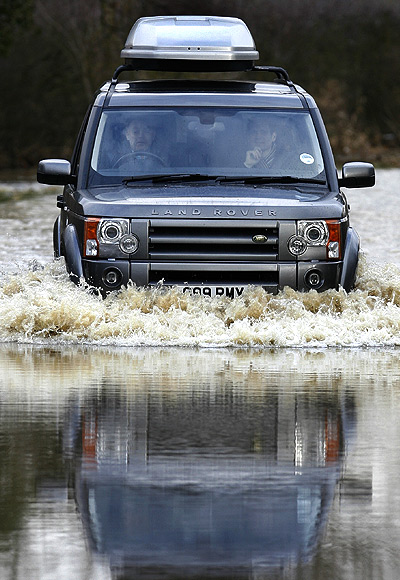 A vehicle is driven through flood waters.
