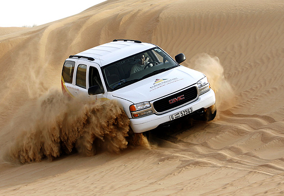 A four-wheel vehicle carrying tourists drives down a dune in the Dubai desert.