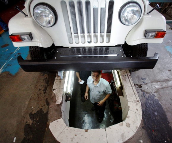 An employee looks out from a pit under an assembled Mahindra Bolero vehicle at the company's manufacturing plant on the outskirts of Mumbai.