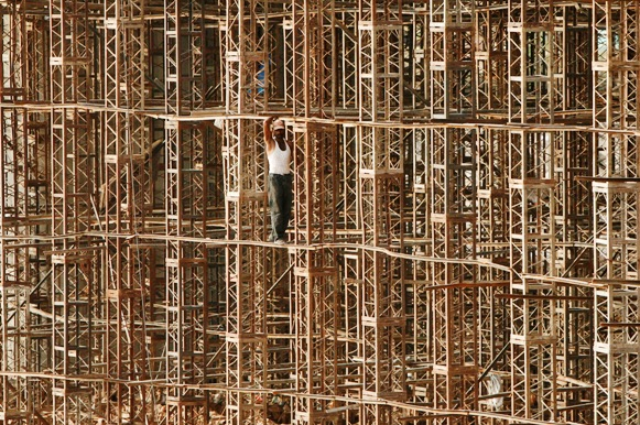 A construction worker stands on scaffolding at the site of a bridge.
