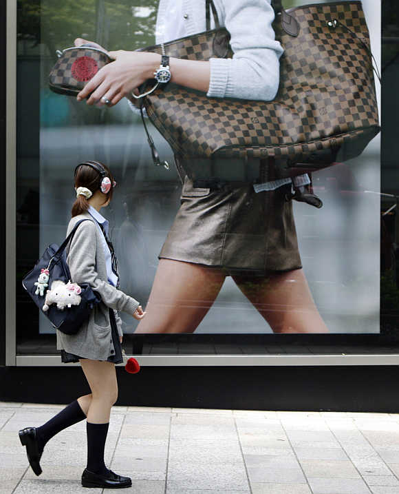 A student in a school uniform walks past a luxury brand store in a Tokyo shopping district, Japan.