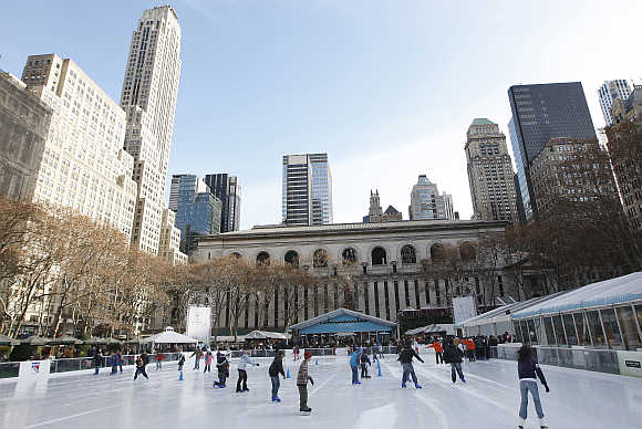 Children rush out onto a freshly resurfaced ice rink set up in Bryant Park, New York City, United States.