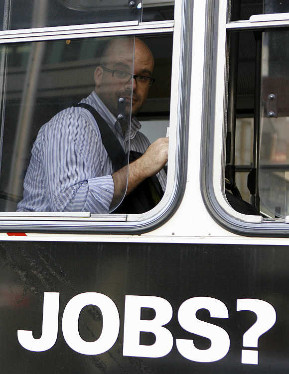 A man sits in a bus with an advertisement for jobs in central Sydney, Australia.