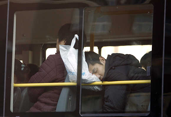 A commuter on a public bus sleeps while resting his head on a shopping bag in central Beijing, China.