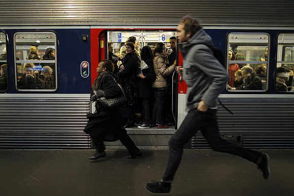 Commuters run to catch a train at Gare Saint Lazare station in Paris, France.