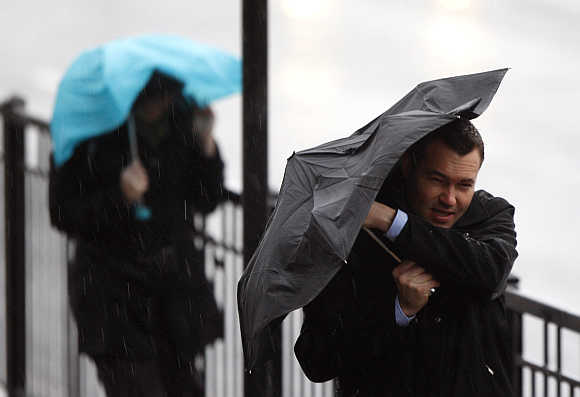 Commuters struggle through heavy rain and strong winds across London Bridge to the city of London, United Kingdom.