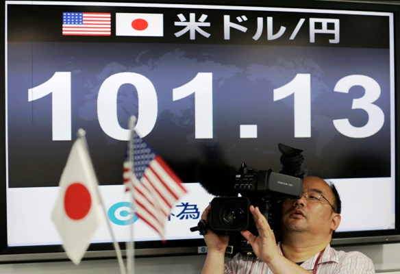 A TV cameraman films in front of a monitor displaying the Japanese yen's exchange rate against the US dollar at a foreign exchange company in Tokyo on May 10, 2013.