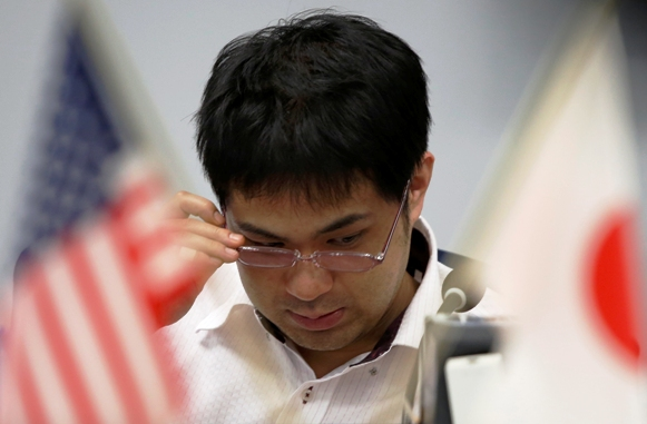 An employee of a foreign exchange trading company adjusts his glasses between the U.S. and Japanese national flags in Tokyo.