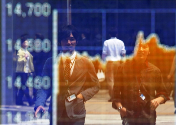 Passersby are reflected on an electronic board displaying a graph showing recent movements of Japanese market indices outside a brokerage in Tokyo.