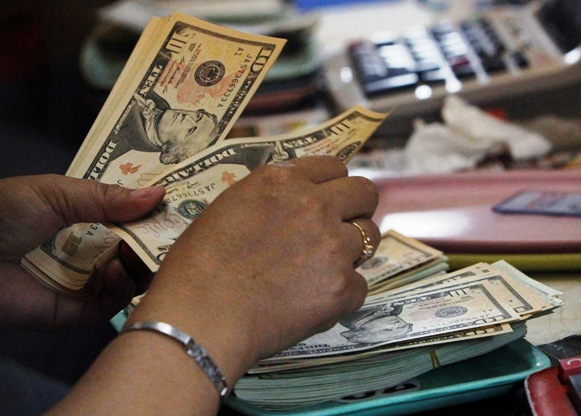 A worker counts US dollar bills inside a money changer in Manila.