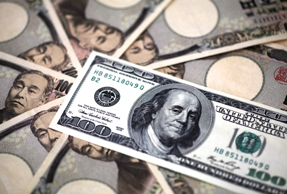 A US one-hundred dollar bill (C) and Japanese 10,000 yen notes are spread in Tokyo.