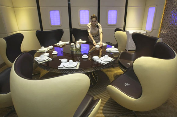 A waitress poses as she arranges a dining table inside a private room of an A380 theme restaurant.