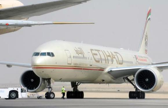 An engineer walks near an Etihad Airways aircraft at Abu Dhabi International Airport.